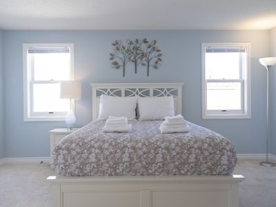 master bedroom with queen bed and ensuite bathroom on the main floor