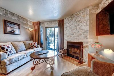 Relaxing living room cozy wood burning fireplace large screen TV - ParkCityLodging_Snowcrest 114_Living_1