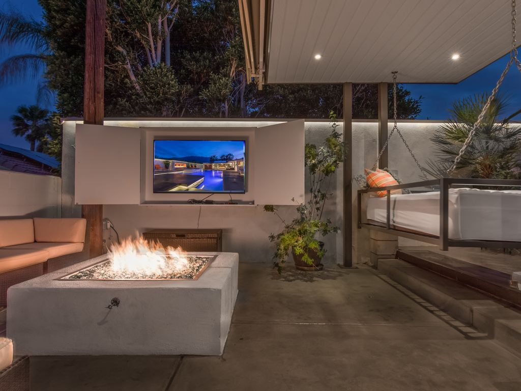 outdoor living area at night sofa firepit lcd tv grill swinging