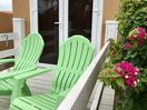 Relax in comfortable outdoor chairs on the private balcony of the main bedroom.