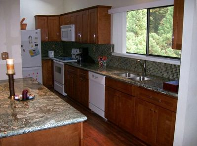 Full kitchen with maple cabinets and granite slab counters/island