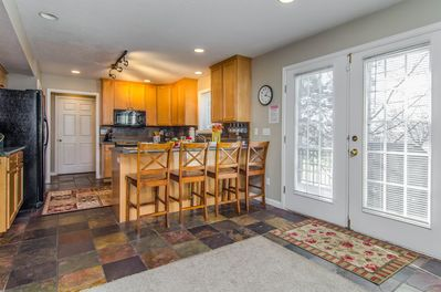 Beautiful kitchen with slate floors and bar with door to hot tub