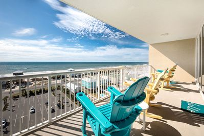 Wide balcony overlooking the Gulf of Mexico with 4 rocking Adirondack chairs