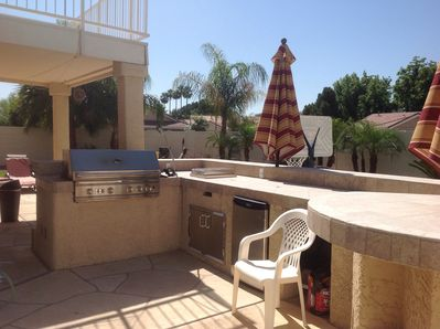 Outdoor kitchen with professional grade gas grill, side burner, small fridge