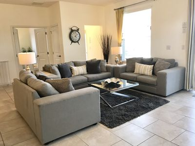 """Modern living room with spacious seating and large 60"""" TV"""