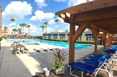 POOL AREA WITH COVERED SEATING, PICNIC TABLES, BBQ GRILLS AND 2 HOT TUBS