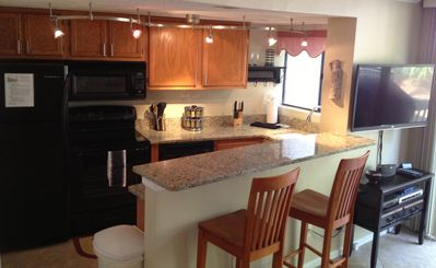 Open kitchen, bar seating, and new flat screen TV.