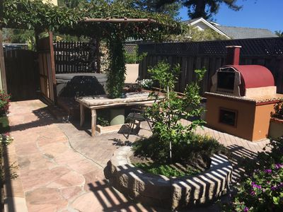 Hot tub and pizza oven on property shared with owners. Large table with seating.