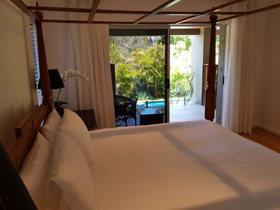 Beautiful main bedroom with own balcony over looking pool and tropical garden.