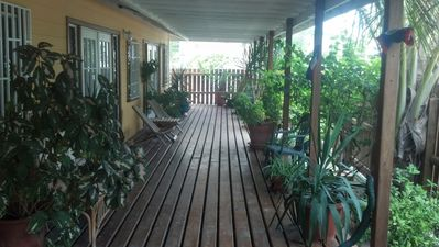 Lush welcoming covered deck.