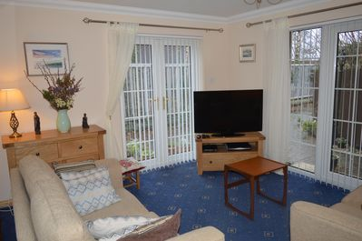 Living room with patio doors, desk, TV with Sky Sports and Movies, French doors