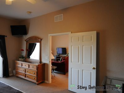 The master bedroom includes a large dresser, LED TV and ceiling fan.