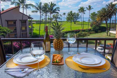 Pineapple, wine glasses, and plates set on a patio table facing the ocean and palm trees
