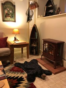 A plush bear rug adds authenticity to the electric fireplace. Not a real bear!