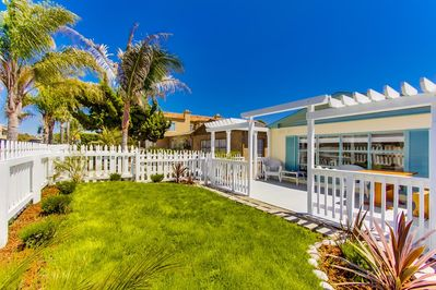 From the side of the yard you see the white picket fence along the sidewalk.