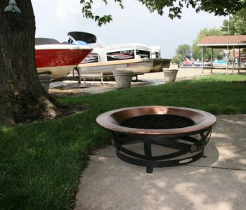 Copper firepit; do not stack wood on grass.  Buy wood at Lakeview Hardware