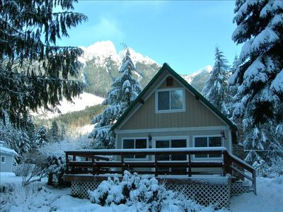 Winter finds the cabin covered in snow and surrounded by snow capped mountains.