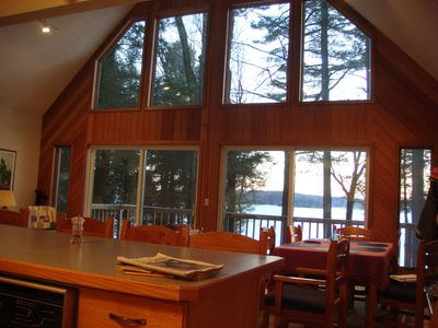 View of lake through window, table for 6 on right, 4 bar stools at counter