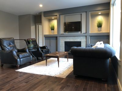 Two comfortable recliners and gas fireplace overlooking a wooded area.