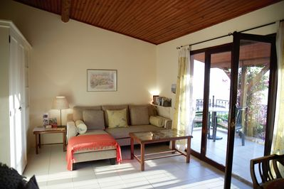 L-shaped sofa, doors to terrace with sea view
