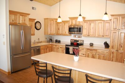 Kitchen with new stainless appliances, hickory cabinets and a breakfast bar.