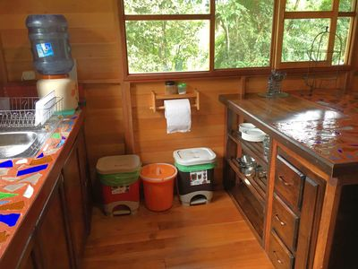 View of kitchen with essential dishware, recycling, garbage & compost bin!