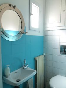 Toilet with a small window unoverlooked. A closet with cleaning supplies & tools