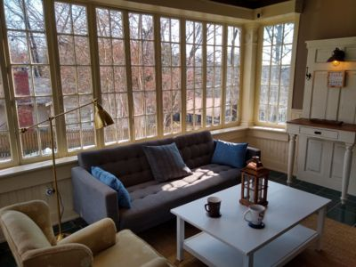 well lit sunroom great for morning coffee. also sofa converts to bed if needed.