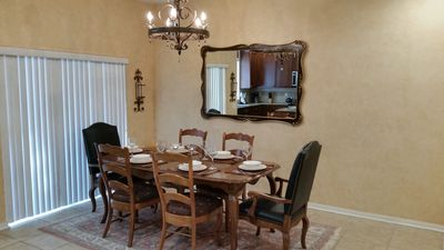 Dining room table with place setting for 6 guests and sliding doors to patio
