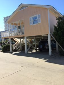 Side view of house, parking underneath, porch