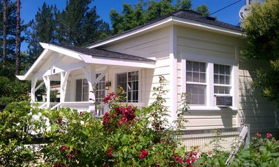 Front of house & veranda nestled behind sweet smelling roses & honeysuckle vines