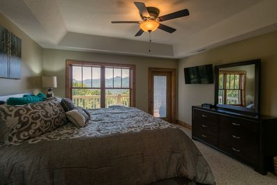 Master bedroom with tray ceiling, view and TV