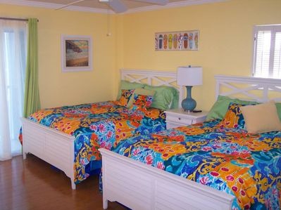 Guest bedroom with 2 double beds; private bathroom and private walkout to lanai.