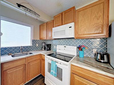 Kitchen - The updated kitchen has marble countertops and full-size appliances.