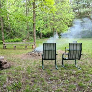 Outdoor fire pit with wood provided.