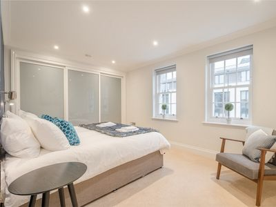 Master bedroom with super king size bed, floor to ceiling wardrobes and a modern ensuite bathroom.