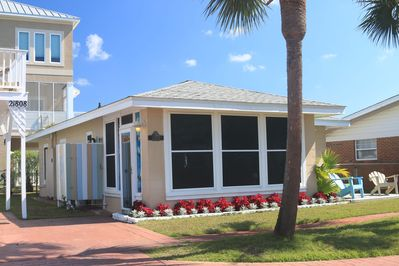 Meticulously maintained landscaping and lush grass surround our beach cottage.