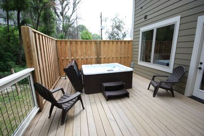 Four person hot tub on outside deck overlooking mountain stream
