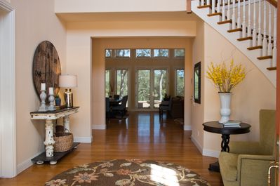 Entryway looking out living room windows toward fountain and view of hills