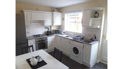 Very well equipped kitchen with table and chairs, looking out to the garden area