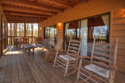 Expansive porch with plenty of seating, rocking chairs, swing and tables
