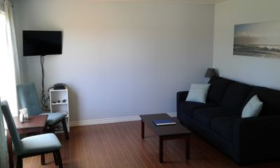 Freshly painted living room, with new sofa bed, chairs, décor, T.V. and DVD player.
