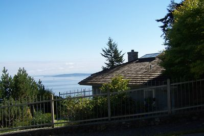 The cottage is nestled against the cliff overlooking the Salish Sea and Cascades