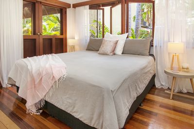 Beautiful master bedroom with luxurious king size bed, looking out onto gardens