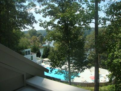 View of condo pool & lake in background, from porch that seats 2 for meal/drinks