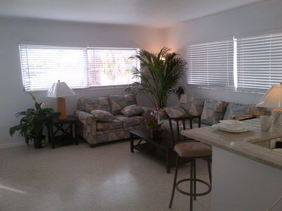 large open den with flat screen TV full size sofa and love seat.
