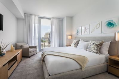 Master Bedroom of our 2 bedroom apartment which includes a LED TV, Balcony and walk-in closet.
