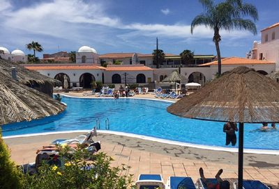 Spacious community pool area with plenty of sunbeds