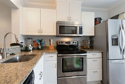 Kitchen with updated cabinets, stainless appliances, granite counter tops.
