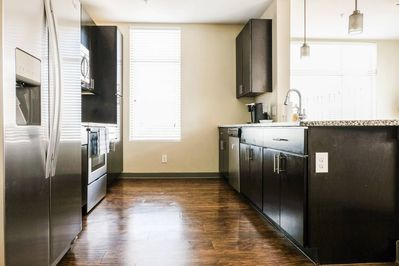 Spacious kitchen with dishes, cups, utensils and basic cookware.